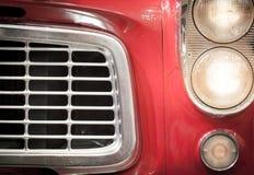 Fermez-vous du gril et des phares du véhicule rouge Images stock