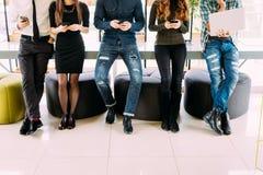 Fermez-vous du groupe d'amis se tenant sur la table et passant en revue dans leurs divices dans la chambre moderne Photo stock