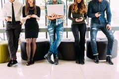 Fermez-vous du groupe d'amis se tenant sur la table et passant en revue dans leurs divices dans la chambre moderne Ensemble amuse Photos libres de droits