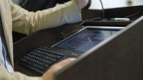 Fermez-vous du haut-parleur se tenant au podium et travaillant sur l'ordinateur pour présenter un exposé banque de vidéos