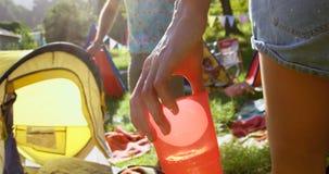 Fermez-vous du hippie de femme donnant un verre d'eau à son ami banque de vidéos
