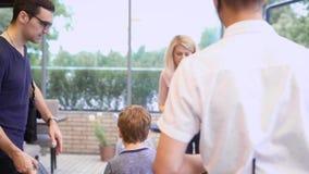 Fermez-vous du jeune serveur masculin se tenant dans le restaurant avec le menu et souhaitant la bienvenue à des invités Famille  banque de vidéos