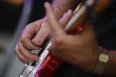 Fermez-vous du joueur de guitare jouant un solo photographie stock