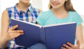 Fermez-vous du livre de lecture heureux de filles à la maison Photo libre de droits