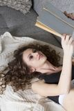 Fermez-vous du livre de lecture menteur de femme détendant à la maison photo stock