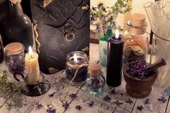Fermez-vous du livre magique, des pots de fleur et en verre secs et des bougies brûlantes sur la table Images stock