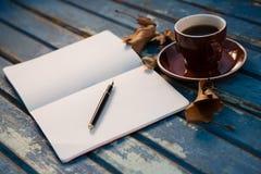 Fermez-vous du livre ouvert par la tasse de café Photographie stock