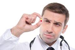 Fermez-vous du médecin semblant la petite pilule jaune-rouge Photographie stock