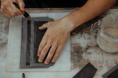 Fermez-vous du maître faisant le portefeuille en cuir avec la brosse et la colle Maître fait main au travail dans l'atelier local images libres de droits