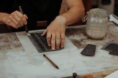 Fermez-vous du maître faisant le portefeuille en cuir avec la brosse et la colle Maître fait main au travail dans l'atelier local photo libre de droits