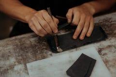 Fermez-vous du maître faisant le portefeuille en cuir avec la brosse et la colle Maître fait main au travail dans l'atelier local photos libres de droits