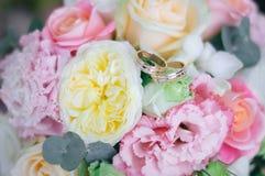 Fermez-vous du mariage coloré de ressort avec des anneaux de mariage là-dessus Photos stock