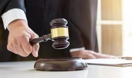 Fermez-vous du ` masculin s de main d'avocat ou de juge heurtant le marteau dessus ainsi photographie stock