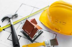 Fermez-vous du modèle de maison avec des outils de bâtiment Images stock