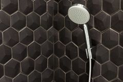 Fermez-vous du nouveau pommeau de douche de pluie dans la salle de bains sur un fond des tuiles noires photos libres de droits