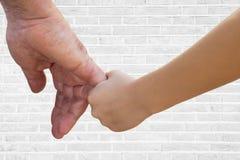 Fermez-vous du père et du fils tenant des mains contre le mur de briques blanc Photographie stock