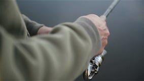 Fermez-vous du pêcheur dans des rotations d'imperméable tournant la bobine de pêche dans le mouvement lent clips vidéos