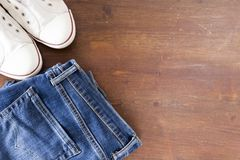 Fermez-vous du pantalon et des espadrilles de jeans sur le fond en bois Images stock
