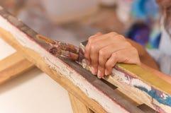 Fermez-vous du peintre tenant le pinceau et le cadre, à un arrière-plan de peinture de studio Image libre de droits