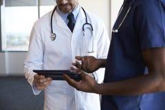 Fermez-vous du personnel hospitalier passant en revue des notes sur la Tablette de Digital photo stock