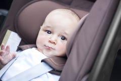 Fermez-vous du petit bébé garçon dans une voiture dans un siège d'enfant Image stock