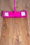 Fermez-vous du plancher de parquet en bois avec le balai rose - avant ensuite image stock