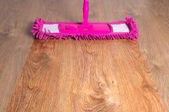 Fermez-vous du plancher en bois avec le balai rose - avant ensuite photographie stock libre de droits