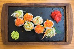 Fermez-vous du plateau en bois savoureux des sushi d'un plat noir se tenant sur une table en bois dans un restaurant japonais Photographie stock libre de droits