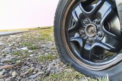 Fermez-vous du pneu crevé sur une voiture sur la route de gravier images stock