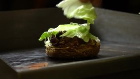 Fermez-vous du processus de faire cuire un hamburger dans une cuisine ouverte d'aliments de préparation rapide Le cuisinier fait  banque de vidéos
