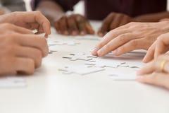 Fermez-vous du puzzle se réunissant d'équipe diverse de travail ensemble image libre de droits