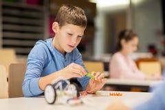 Fermez-vous du robot de bâtiment de garçon à l'école de robotique Photographie stock libre de droits