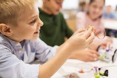 Fermez-vous du robot de bâtiment de garçon à l'école de robotique Image stock