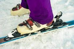 Fermez-vous du skieur de skieur de skieur de ski sur la couleur blanc-violette de neige photos stock