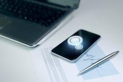 Fermez-vous du smartphone, de l'ordinateur portable et du stylo sur la table Photographie stock libre de droits