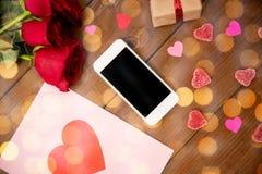 Fermez-vous du smartphone, du cadeau, des roses rouges et des coeurs Photos libres de droits