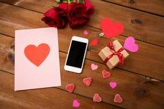 Fermez-vous du smartphone, du cadeau, des roses rouges et des coeurs Photos stock