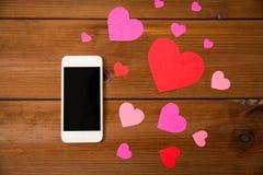 Fermez-vous du smartphone et des coeurs sur le bois Photographie stock