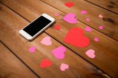 Fermez-vous du smartphone et des coeurs sur le bois Images stock