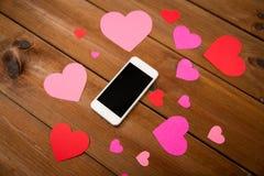 Fermez-vous du smartphone et des coeurs sur le bois Image stock