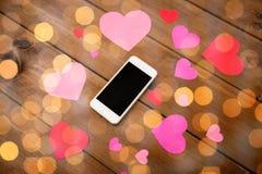 Fermez-vous du smartphone et des coeurs sur le bois Photographie stock libre de droits