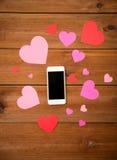 Fermez-vous du smartphone et des coeurs sur le bois Photo stock