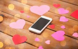 Fermez-vous du smartphone et des coeurs sur le bois Photo libre de droits
