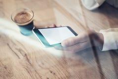 Fermez-vous du smartphone générique de conception avec l'écran vide se tenant dans la main femelle Mettez en forme de tasse l'exp Photo libre de droits