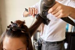 fermez-vous du styliste faisant la coiffure au salon image stock