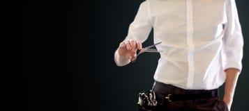 Fermez-vous du styliste masculin avec des ciseaux au-dessus de noir Photos stock