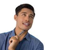 Fermez-vous du stylo de participation réfléchi d'homme d'affaires tout en regardant loin Photographie stock
