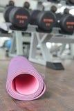 Fermez-vous du tapis roulé de yoga sur un plancher en bois photographie stock