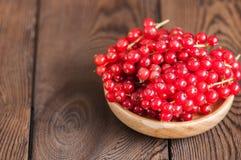 Fermez-vous du tas des groseilles rouges crues fraîches dans un plat sur un woode Images libres de droits