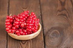 Fermez-vous du tas des groseilles rouges crues fraîches dans un plat sur un woode Images stock
